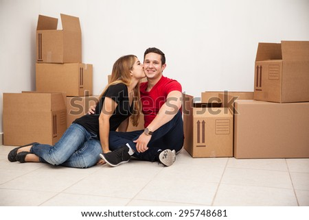 Cute young couple moving into their first home and sitting in a room full of boxes - stock photo