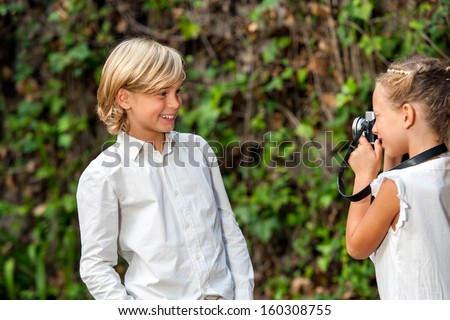 Cute young couple playing around with camera at photo shoot outdoors. - stock photo