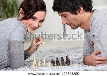 cute young couple playing chess together