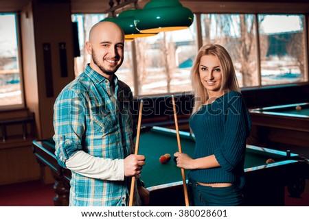 Cute young couple plays billiard and having some fun. American pool billiard. Billiard sport concept. Pool billiard game. - stock photo