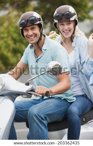 Cute young couple riding on scooter on a sunny day in the city - stock photo