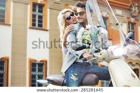 Cute young couple riding scooter together - stock photo