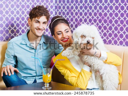 Cute young couple sitting at the table with a puppy  - stock photo