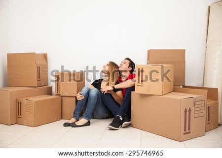 Cute young couple sitting in the floor of their new home while unpacking and looking towards copy space