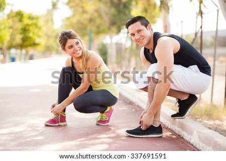 Cute young couple tying their shoes and getting ready for some running and working out together - stock photo
