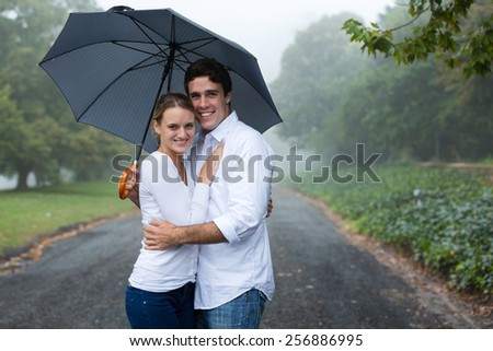 cute young couple under an umbrella in the mist - stock photo