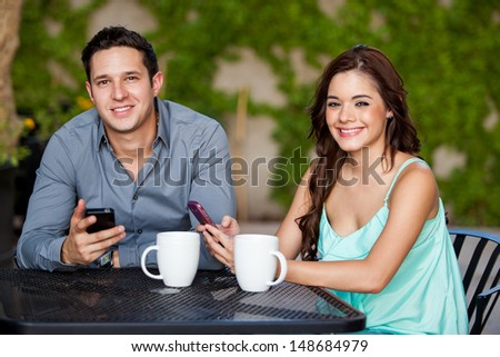 Cute young couple updating their social network status during a date at a cafe