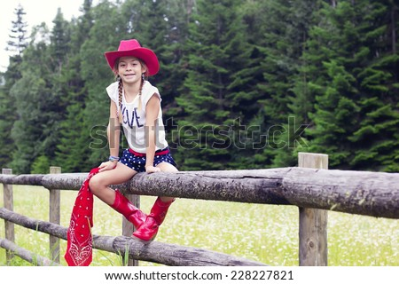 Cute young cowgirl portrait on a wooden fence - stock photo