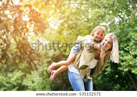 Cute young daughter on a piggy back ride with her mother. Looking at camera.