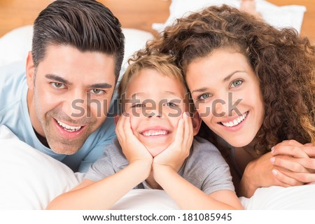 Cute young family lying on bed together smiling at camera at home in bedroom - stock photo