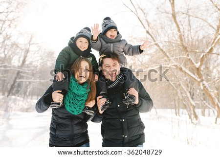 Cute young family with twins and pregnant young mother having fun in winter park on a bright day hugging each other and smiling  - stock photo