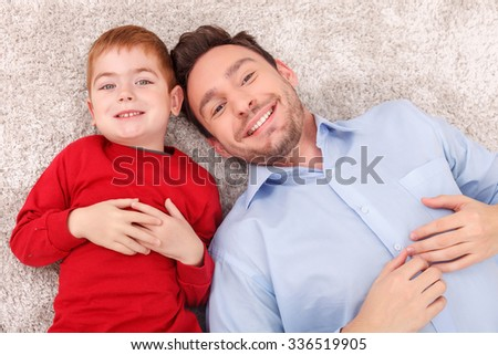 Cute young father and his son are lying on flooring near each other. They are looking forward and smiling - stock photo