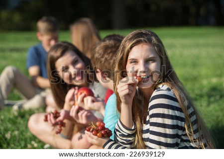 Cute young female eating grapes with group outdoors - stock photo