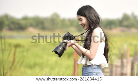 Cute young female photographer with camera outdoors at the park - stock photo