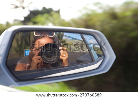 Cute young female photographer with camera. Woman reflected in the rearview mirror of a car on a summer day (out of focus). - stock photo