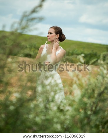 Cute young female posing by a farm - stock photo