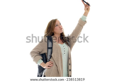 Cute young female student in sweater carrying a backpack in studio - taking selfie on cell phone - stock photo