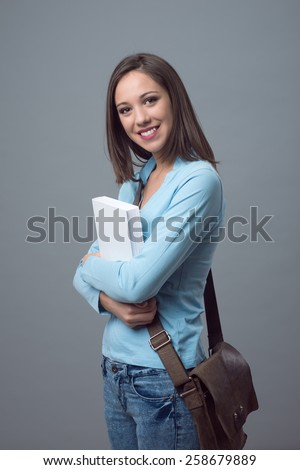 Cute young female teenager student holding a book and smiling at camera - stock photo