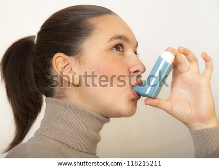 Cute young female using an asthma inhaler for preventing attacks - stock photo