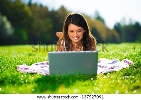 Cute young female with a laptop lying on grass