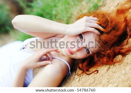 Cute young female with red hairs lying on ground - stock photo