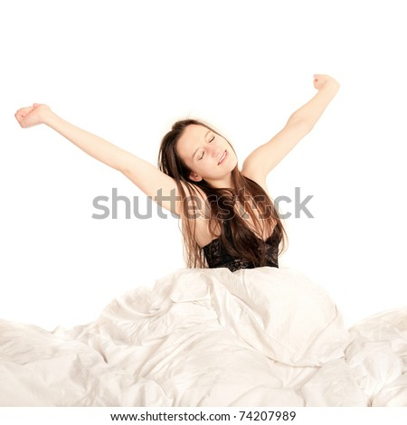 Cute young female yawning and stretching in bed in front of white background - stock photo