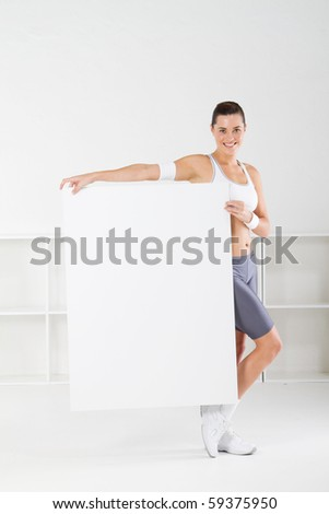 cute young fitness woman holding a white board - stock photo