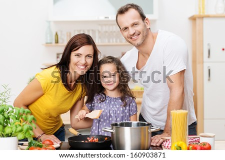 Cute young girl cooking with her parents in the kitchen as the three pose with broad smiles alongside the stove and spaghetti ingredients - stock photo