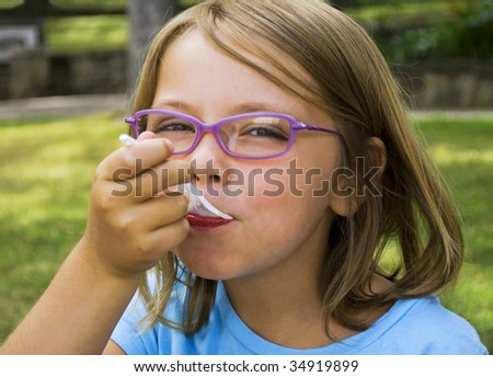 Cute young girl cooling down with some ice-cream in the park - stock photo