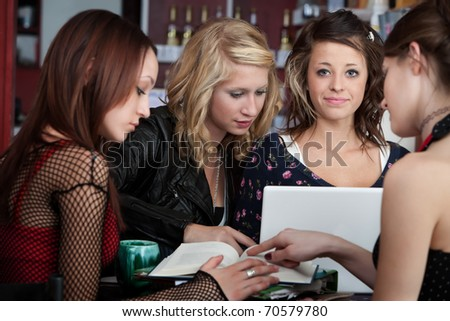 Cute young girl doing homework with friends in a cafe