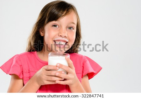 Cute young girl drinking and holding a glass of milk with a milk moustache - stock photo