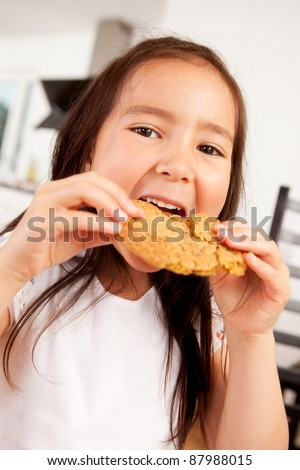 Cute young girl eating a large monster cookie - stock photo