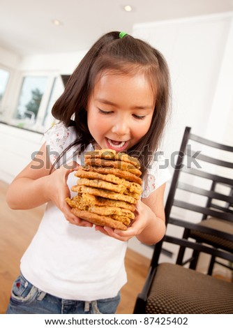 Cute young girl eating stack of large chocolate chip cookies - stock photo