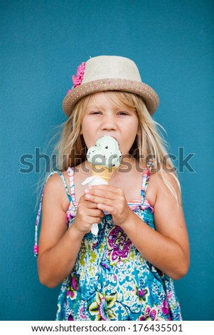 Cute young girl eating vanilla ice cream in cone outside against blue wall background - stock photo