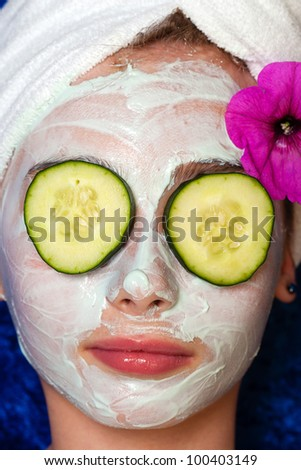 Cute young girl getting pampered with a deluxe spa treatment including facial mask and sliced cucumber over her eyes.