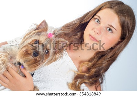 Cute young girl holding a dog on a leash