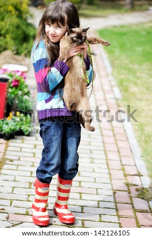 Cute young girl holding her kitty during a walk outside - stock photo