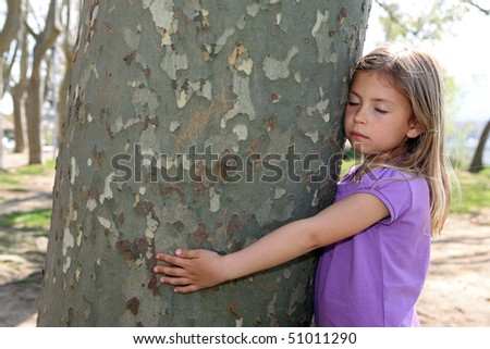 Cute young girl hugging a tree trunk