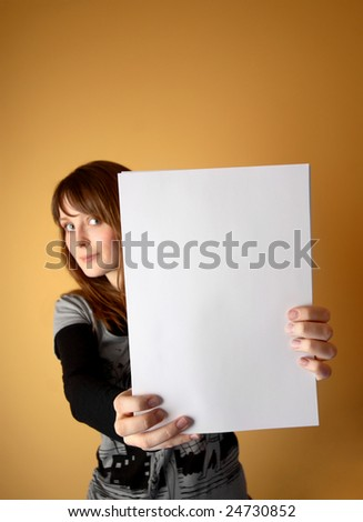 Cute young girl is holding sheets in front of her. Focus on sheets. - stock photo