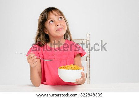 Cute young girl kid holding bowl of breakfast cereal cornflakes looking up, healthy eating and diet concept - stock photo