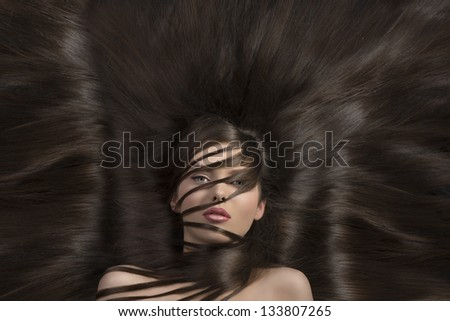 cute young girl laying with a lot of hair all around and some locks on face - stock photo
