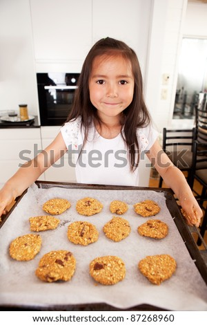 Cute young girl looking at camera with baking sheet full of raw cookies - stock photo
