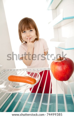Cute young girl looking in open refrigerator deciding between healthy apple and unhealthy hot dog. - stock photo