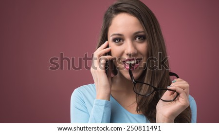 Cute young girl on the phone biting glasses - stock photo
