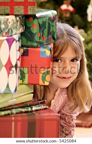 Cute young girl peeking from side of Christmas presents - stock photo