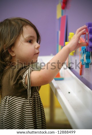 Cute young girl playing with educational toys at school. Vertically framed shot - stock photo