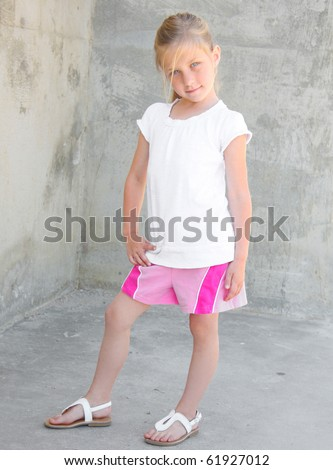 Cute young girl posing in front of a cement structure. - stock photo