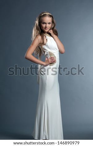 Cute young girl posing in white dress and tiara