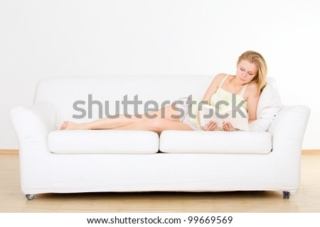 cute young girl reading on couch at home - stock photo