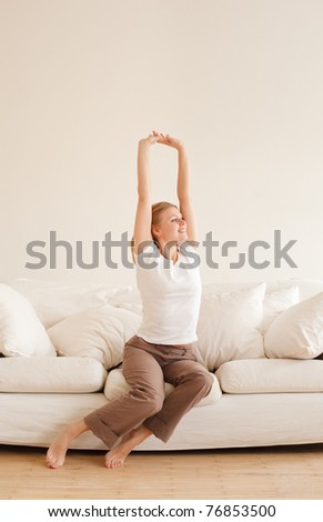 cute young girl relaxing and stretches on couch at home